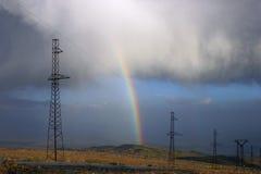 Líneas eléctricas con el arco iris Imagen de archivo libre de regalías