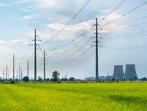 Líneas eléctricas de alto voltaje En campos del verde del primero plano, en backgro Imágenes de archivo libres de regalías