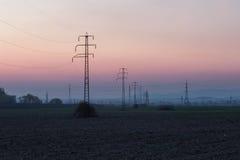 Líneas eléctricas de alto voltaje en la puesta del sol Imágenes de archivo libres de regalías