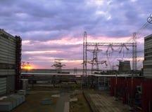 Líneas eléctricas de alto voltaje en la puesta del sol en la central nuclear Imagenes de archivo