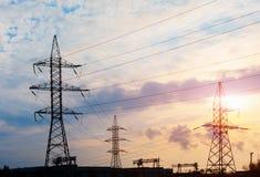 Líneas eléctricas de alto voltaje en la puesta del sol Estación de la distribución de la electricidad Torre eléctrica de alto vol imagen de archivo libre de regalías
