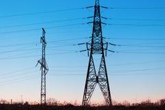 Líneas eléctricas de alto voltaje en la puesta del sol Estación de la distribución de la electricidad foto de archivo