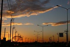 Líneas eléctricas de la electricidad en la puesta del sol Foto de archivo