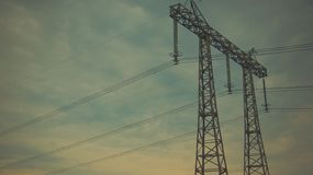 Líneas eléctricas de la energía en el cielo azul fotografía de archivo