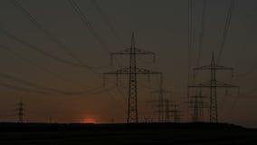 Líneas eléctricas de la puesta del sol de Timelapse y turbina de viento almacen de metraje de vídeo