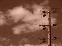 Líneas eléctricas de la sepia con las nubes Imagen de archivo