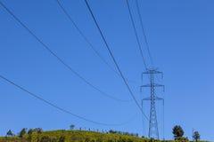 Líneas eléctricas eléctricas en una colina antes de un cielo azul Foto de archivo