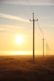 Líneas eléctricas en el amanecer en la niebla Imagen de archivo