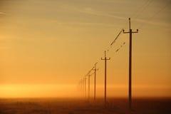 Líneas eléctricas en el amanecer en la niebla Foto de archivo
