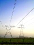 Líneas eléctricas en la niebla de la mañana Imagenes de archivo