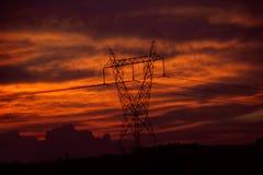Líneas eléctricas eléctricas en la puesta del sol foto de archivo