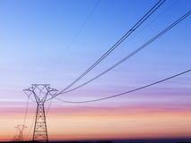 Líneas eléctricas en la puesta del sol Fotografía de archivo