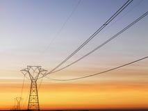 Líneas eléctricas en la puesta del sol Fotos de archivo libres de regalías