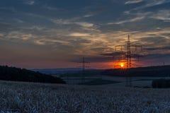 Líneas eléctricas en la puesta del sol Foto de archivo libre de regalías