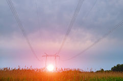 Líneas eléctricas en un campo en la puesta del sol, amanecer Fotos de archivo