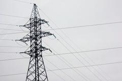 Líneas eléctricas en un campo nevoso en el campo en un fondo blanco imágenes de archivo libres de regalías