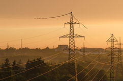 Líneas eléctricas iluminadas por el sol poniente Fotografía de archivo libre de regalías
