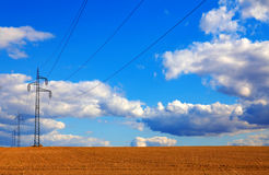 Líneas eléctricas que corren a través de un campo de trigo con el cielo azul Fotos de archivo