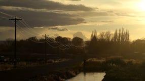 Líneas eléctricas reflejadas en la puesta del sol Imágenes de archivo libres de regalías