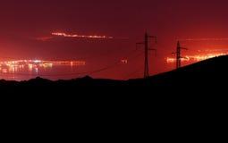 Líneas eléctricas sobre bahía en la noche Imagen de archivo