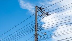 Líneas eléctricas y alambres eléctricos del polo con el cielo azul Foto de archivo