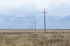 Líneas eléctricas y pilares a través del llano de Tíbet superior Imágenes de archivo libres de regalías