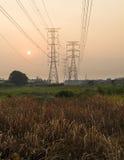 Líneas eléctricas y pilones de Silhoutte en la puesta del sol Foto de archivo