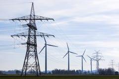 Líneas eléctricas y turbinas de viento Foto de archivo