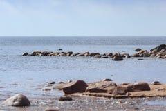 Líneas hermosas de piedras Orilla soleada del golfo de Finlandia Asperja en el agua y las piedras foto de archivo libre de regalías