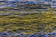 Líneas que brillan intensamente coloreadas en fondo oscuro foto de archivo