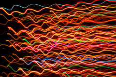 Líneas que brillan intensamente multicoloras onduladas en fondo oscuro Imagenes de archivo