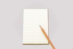 Líneas vacías cuaderno con la cubierta marrón y el lápiz marrón, Foto de archivo