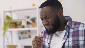 Língua afro-americano chocada da queimadura do homem com a bebida quente, respirando ativamente filme