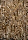 A língua antiga cinzelou na pedra Fotografia de Stock