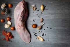 A língua crua da carne ou da carne de porco com vegetais aipo, pimenta, alho, cebola, encontra-se em uma placa de corte, em um cl Imagem de Stock Royalty Free