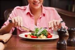 Língua deleitada da mostra da mulher e ir comer a salada com rúcula Imagem de Stock