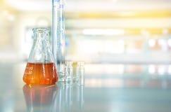Líquido alaranjado na garrafa de vidro com o tubo de ensaio do cilindro no scie químico imagem de stock