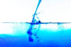 Líquido azul de derramamento na água desobstruída imagens de stock