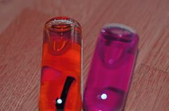 Líquido coloreado en las botellas de cristal Foto de archivo libre de regalías