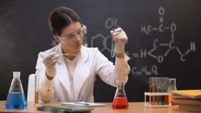 Líquido de gotejamento do estudante da química no tubo de ensaio e nos resultados da escrita, experiência video estoque
