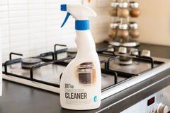 Líquido de limpeza de aço inoxidável marcado resolvido problema na garrafa plástica reciclável e na frente de um hob de aço inoxi fotografia de stock