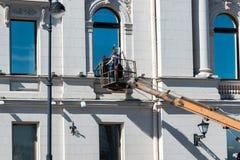 Líquido de limpeza da mulher da janela que trabalha em uma fachada de vidro de construção velha em uma gôndola fotografia de stock royalty free