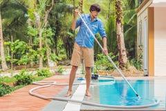 Líquido de limpeza da piscina Homem em uma camisa azul com o equipamento da limpeza para piscinas, ensolarado imagem de stock