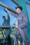 Líquido de limpeza de janela profissional no trabalho fora foto de stock royalty free