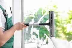 Líquido de limpeza masculino que limpa o vidro de janela com o rodo de borracha dentro Imagem de Stock