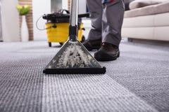 Líquido de limpeza de Person Cleaning Carpet With Vacuum fotos de stock royalty free