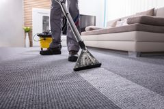 Líquido de limpeza de Person Cleaning Carpet With Vacuum fotografia de stock royalty free