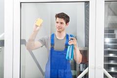 Líquido de limpeza que limpa o vidro da porta Fotografia de Stock Royalty Free