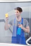Líquido de limpeza que limpa o vidro da porta Imagem de Stock Royalty Free
