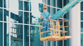 Líquido de limpeza de vidro do homem de funcionamento em uma janela de limpeza do elevador hidráulico filme
